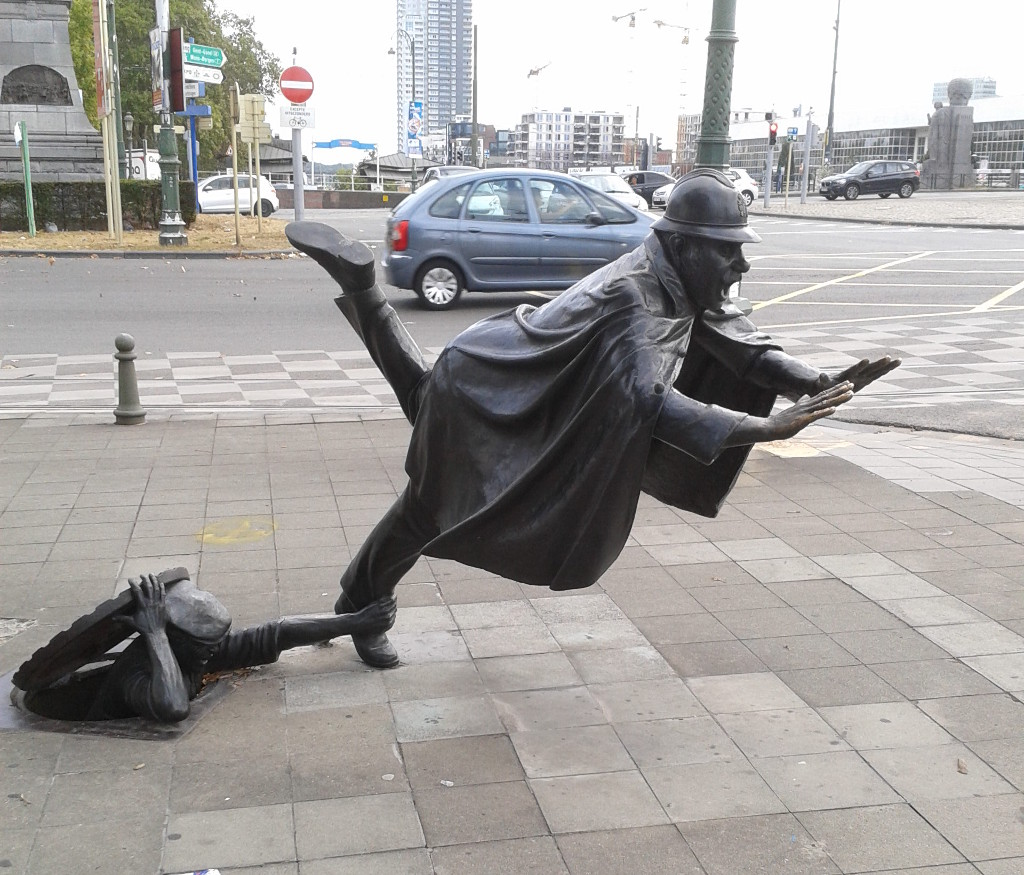 "The statue shown here is ""De Vaartkapoen"" by Belgian artist Tom Frantzen. It is a humorous statue of a policeman being tripped by a man hiding in a sewer manhole. Created in 1985, the statue is located in Sint-Jans-Molenbeek, Belgium which is not far from Hybrid Studios. (see http://www.tomfrantzen.be/en/artr.htm)"